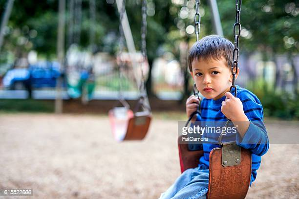 young boy sitting on a swing looking sad - stranger stock pictures, royalty-free photos & images