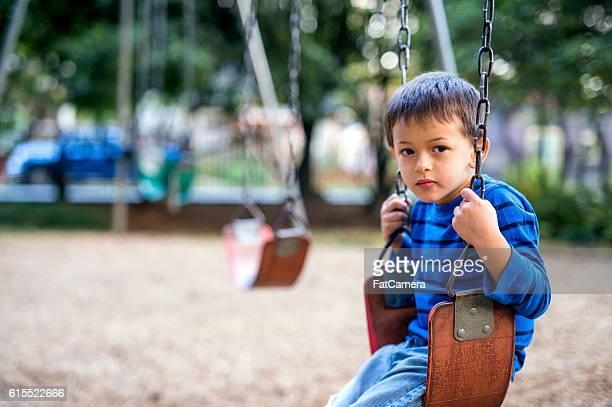 young boy sitting on a swing looking sad - solidão - fotografias e filmes do acervo
