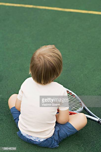 A young boy sitting on a tennis court with a tennis racket, rear view