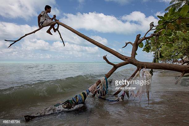 A young boy sitting on a tree branch as the tide comes in with the waves beneath him The people of Kiribati are under pressure to relocate due to sea...
