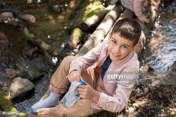 Young boy sitting on a wooden bridge putting his stockings on
