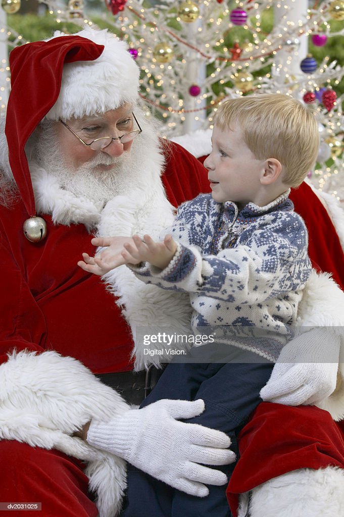 Young Boy Sitting on Father Christmas' Lap : Stock Photo