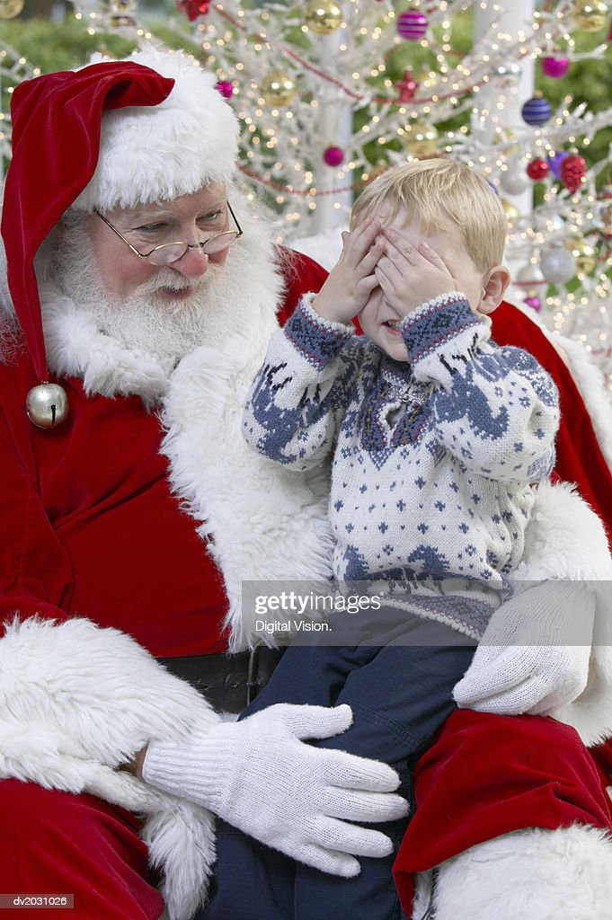 Young Boy Sitting on Father Christmas' Lap With His Hand Over His Eyes : Stock Photo