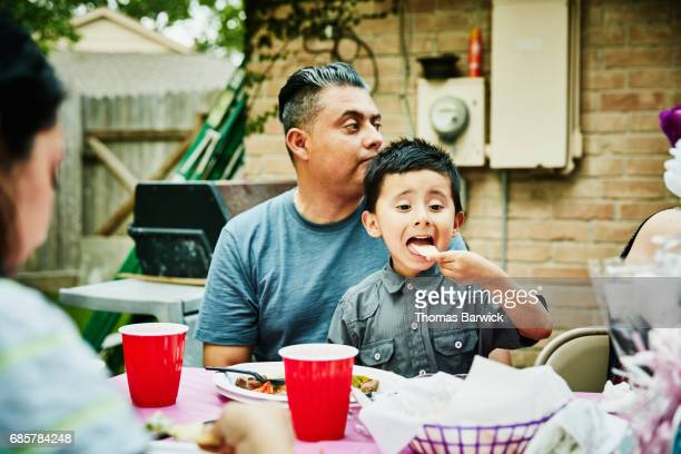 young boy sitting on fathers lap during family birthday party eating tortilla chip - tortilla flatbread stock photos and pictures