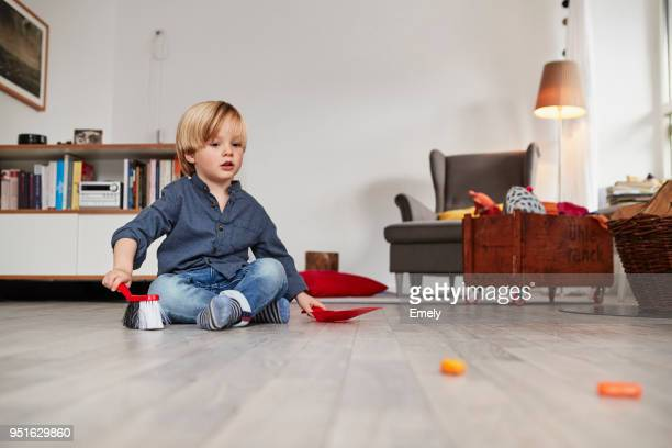 Young boy sitting on floor, holding toy dustpan and brush