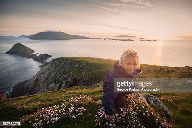 Young boy sitting on hillside, Slea head, County Kerry, Ireland