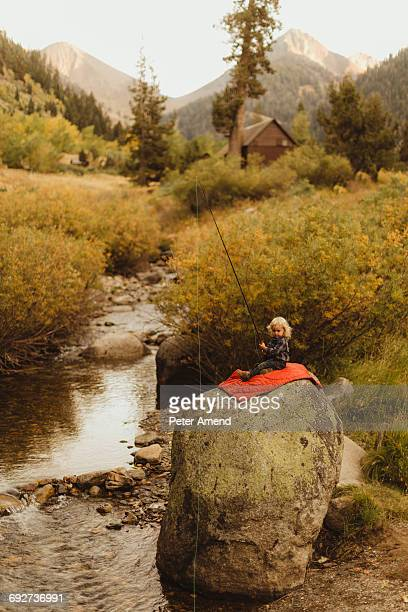 Young boy sitting on rock beside creek, holding fishing rod, Mineral King, Sequoia National Park, California, USA