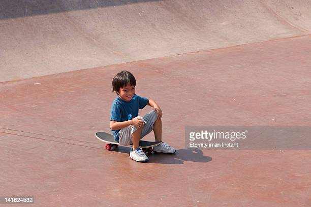 Young boy sitting on skateboard at skateboard park