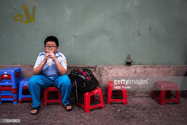 Young boy sitting on small red chair and drinking soda after school,Ho Chi Minh City / Saigon