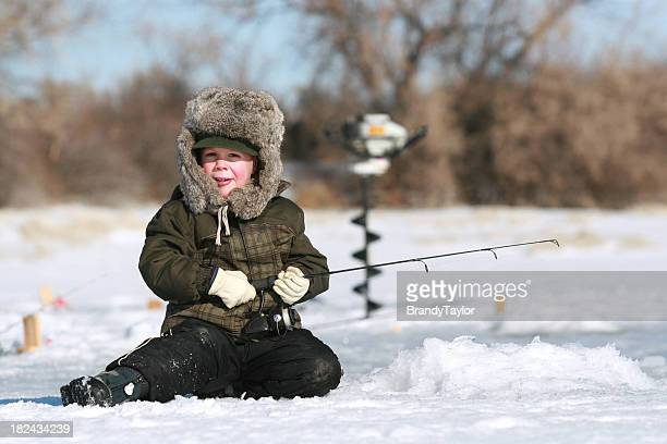 Young boy sitting on snow ice fishing