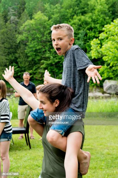 """young boy sitting on teenage girl shoulders outdoors in summer. - """"martine doucet"""" or martinedoucet stock pictures, royalty-free photos & images"""