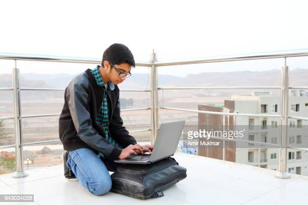 A young boy sitting outdoor on floor using laptop