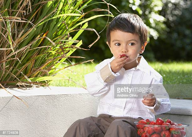 Young boy sitting outdoors with a bowl of strawberries