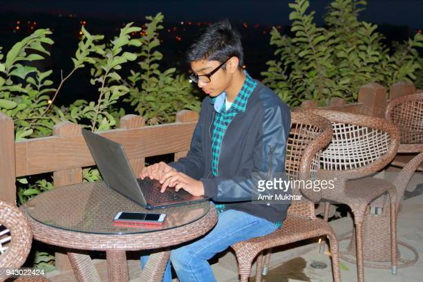 a young boy sitting outside and using laptop on round knitted cane table - school cane stock photos and pictures