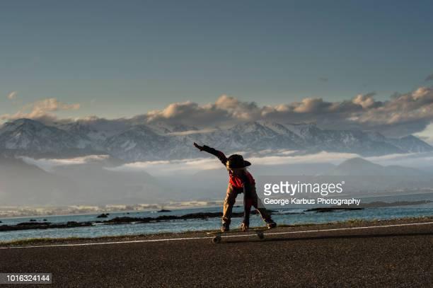 young boy skateboarding along coastal road, kaikoura, gisborne, new zealand - gisborne stock photos and pictures