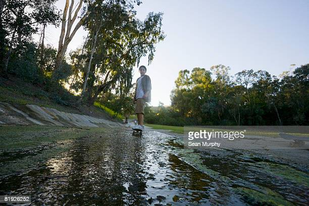 young boy skateboarding in a wet drainage ditch