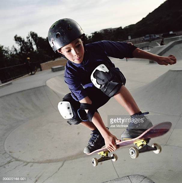 Young boy (9-11) skateboarding in skate park