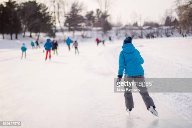 young boy skating on a ice rink - スケート ストックフォトと画像