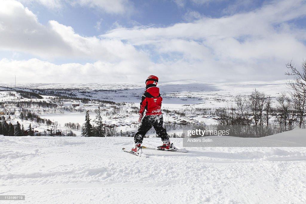 Young boy skiing slalom downhill in sunshine : Stock Photo