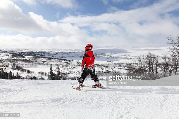 Young boy skiing slalom downhill in sunshine