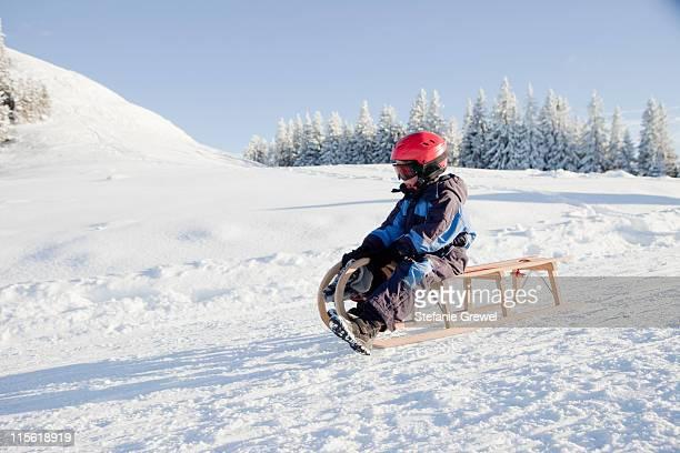 Young boy sledding downhill