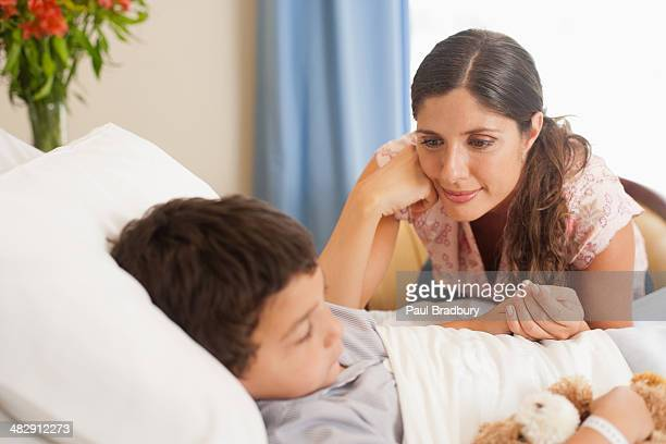 young boy sleeping in hospital bed with teddy bear and woman looking over him - mama bear stock photos and pictures