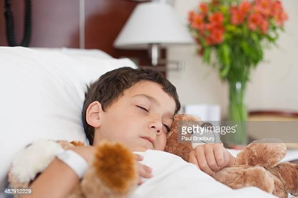 Junge schlafen im Krankenhaus Bett mit teddy Bären