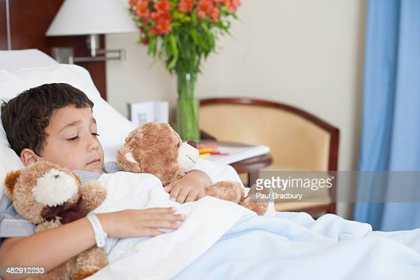 Young boy sleeping in hospital bed with teddy bears