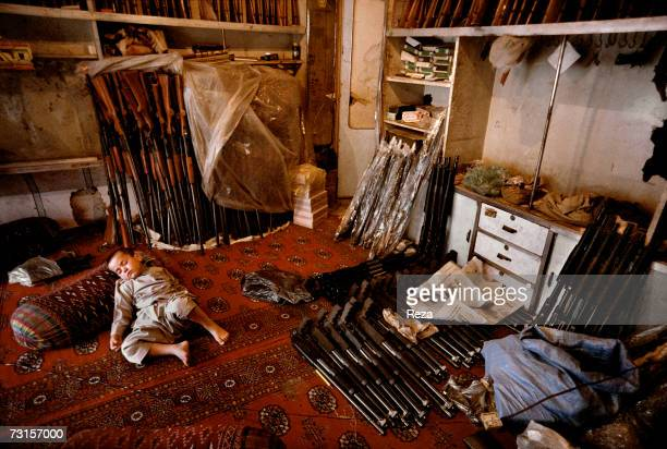 A young boy sleeps in the middle of the guns ready to be sold under the protection of his father and grand father in their factory on July 2004 in...