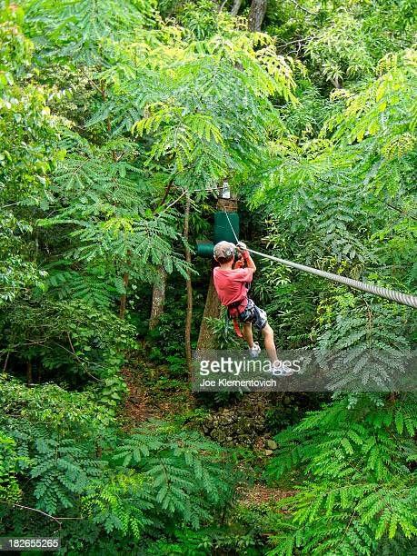 Young boy sliding down a zip line in the jungle of Saint Martin in the Caribbean.