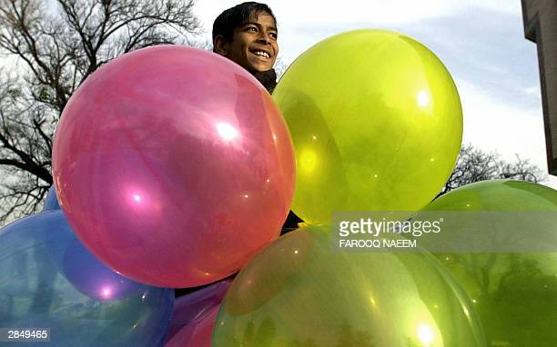 A young boy smiles as he sells balloons in Islamabad 07 January 2004 Pakistani poverty has risen 13 percent over the past 15 years according to a...