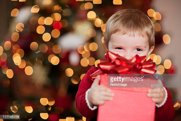 young boy smiles with his christmas present - giving stock photos and pictures
