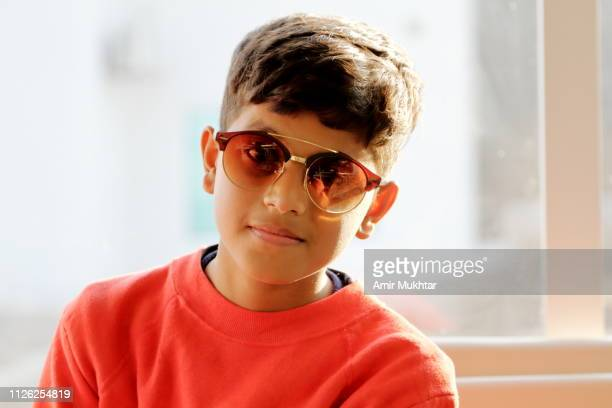 a young boy smiling and looking at the camera while wearing sunglasses - cute pakistani boys stock photos and pictures