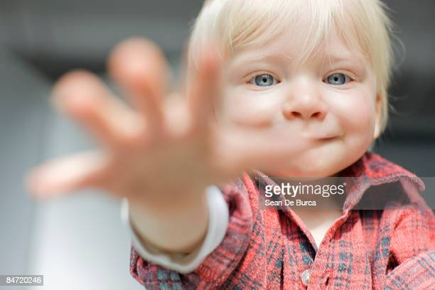young boy smiling and reaching out to camera - tendere la mano foto e immagini stock