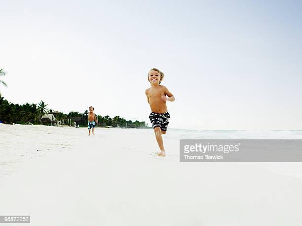 Young boy smiling running down tropical beach