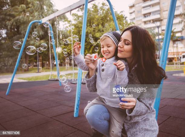 Young boy smiling while his mom blows bubbles at park