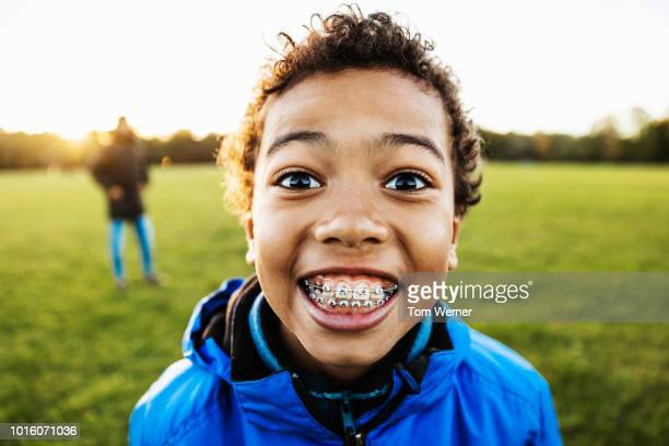 young boy smiling while spending time with dad - brace stock pictures, royalty-free photos & images