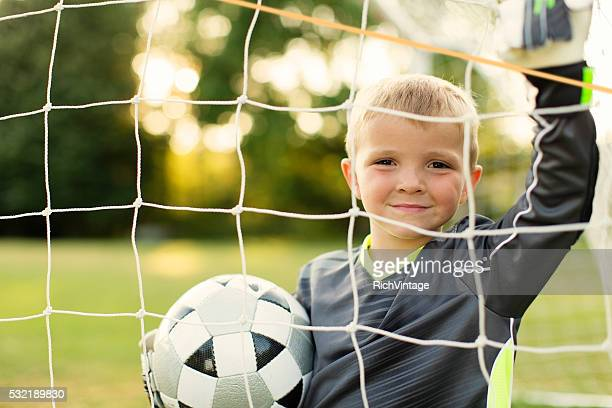 young boy soccer goalie stands holding ball - drive ball sports stock pictures, royalty-free photos & images