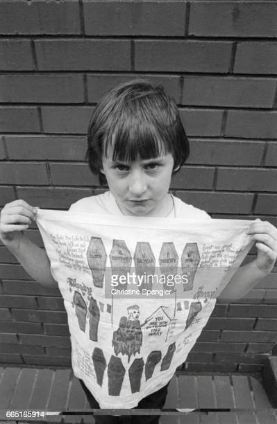 A young boy somberly displays a cloth dedicated to the fourteen civilians killed on January 30 when soldiers from the British Army's 1st Parachute...