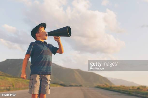 young boy speaks through megaphone - american influenced stock photos and pictures