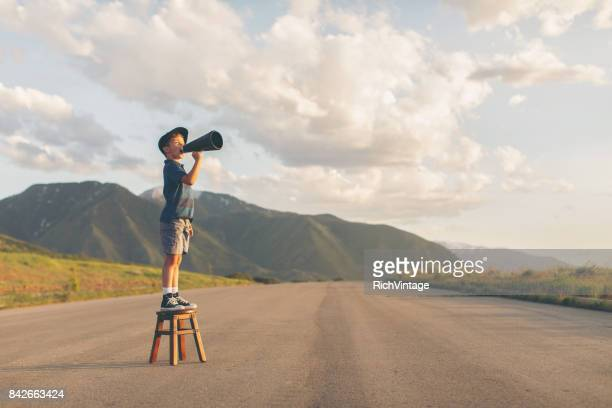 young boy speaks through megaphone - determination stock pictures, royalty-free photos & images