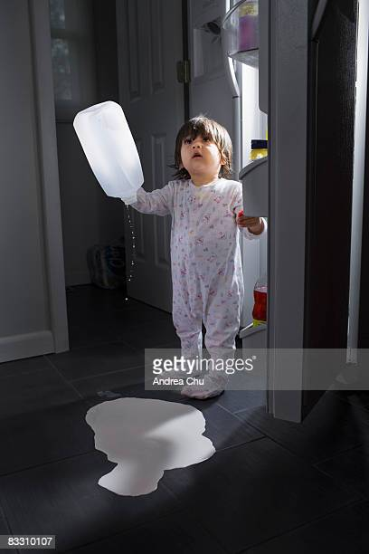Young boy spilling milk on kitchen floor.