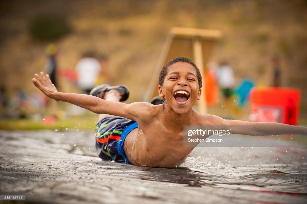 young boy splashing down on a slip n slide : Stock Photo