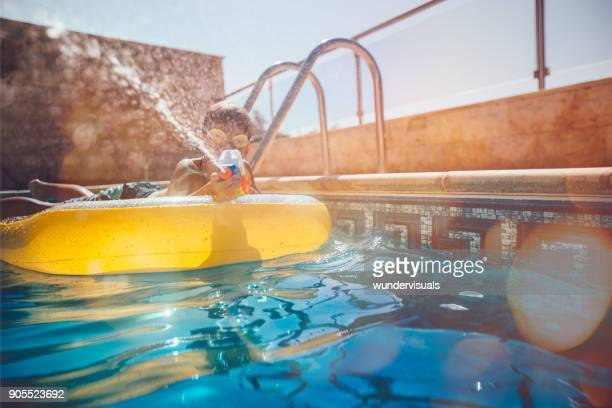 young boy splashing water with water pistol in swimming pool - kids pool games stock pictures, royalty-free photos & images