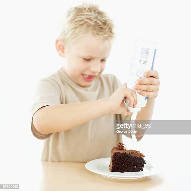 Young boy (7-8) spraying whipped cream on a slice of chocolate cake
