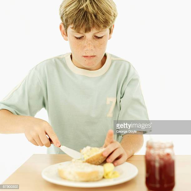 Young boy (12-13) spreading butter over bread