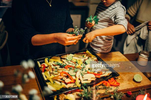 young boy sprinkling fresh herbs on vegetable dish - preparing food stock pictures, royalty-free photos & images