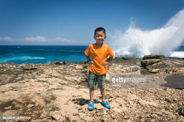 young boy standing akimbo on cliff - arms akimbo stock photos and pictures