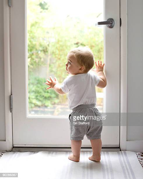 Young boy standing at backdoor, looking off