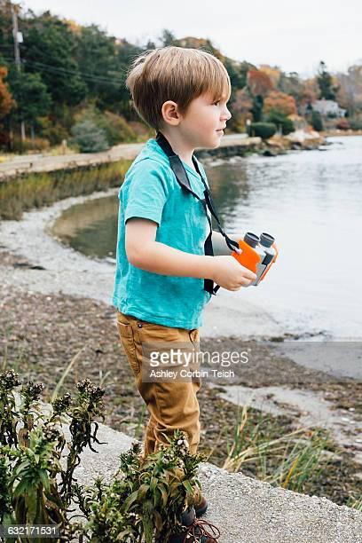 Young boy standing beside lake, holding binoculars